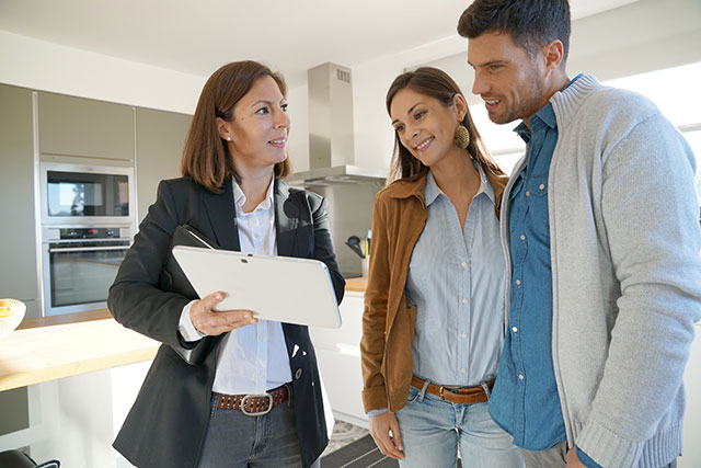 Realtor showing kitchen to clients